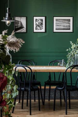 Foto real de sillas negras de pie en una mesa de madera en el elegante interior del comedor con fotos enmarcadas en la pared verde