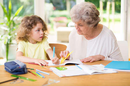 Child doing homework with his grandmother