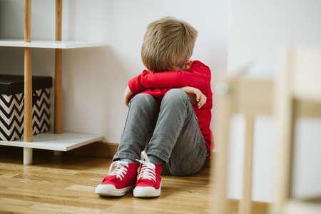 Dziecko z depresją siedzi w kącie pokoju i traci zainteresowanie zajęciami i pracą szkolną Zdjęcie Seryjne