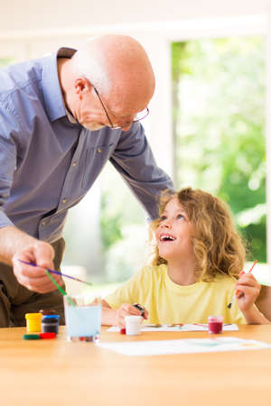 Child painting with his grandfather, spending time together