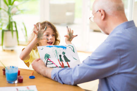 Child showing beautiful drawing to his grandfather