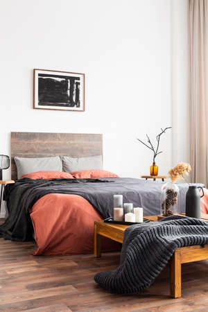 Womans bedroom with natural decorations, woolen blanket and coral bedclothes