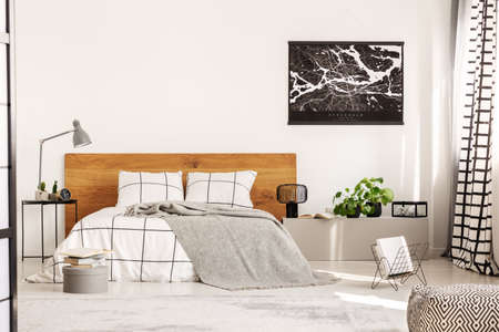 Copy space on white wall with black map in modern bedroom with king size bed with wooden headboard Фото со стока