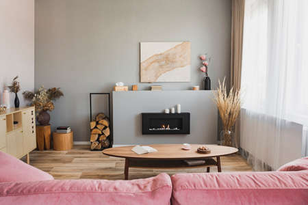 Interni eleganti del soggiorno con divano rosa pastello, tavolino da caffè in legno e caminetto ecologico