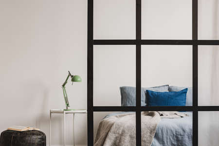 Open plan bedroom interior with partition wall with mullions and mint lamp on nightstand table next to king size bed