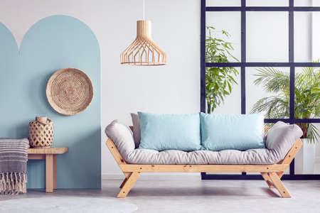 Urban jungle in bright white and blue living room interior with scandinavian futon sofa Archivio Fotografico