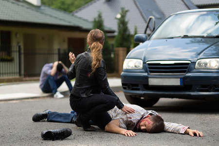 Śmiertelny wypadek samochodowy, zabity mężczyzna leżący na drodze Zdjęcie Seryjne