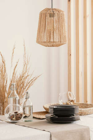Wicker lamp above the table in real photo of dining room