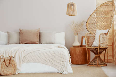 Wicker peacock chair next to wooden nightstand with flowers in vase and king size bed Stock Photo