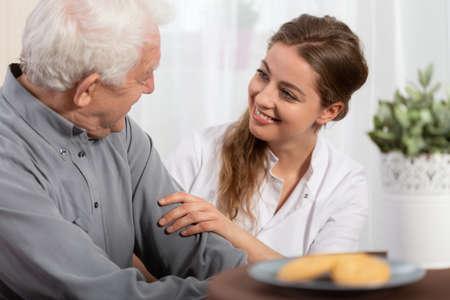 Souriante jeune infirmière assise à table avec un patient âgé Banque d'images