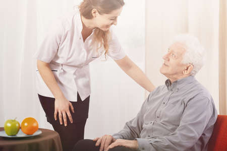 Old man in nursing home with helpful carer at his side