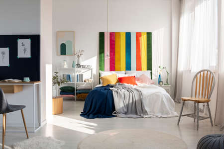 Fashionable bedroom interior with colorful headboard, king size bed, chair and workspace Archivio Fotografico