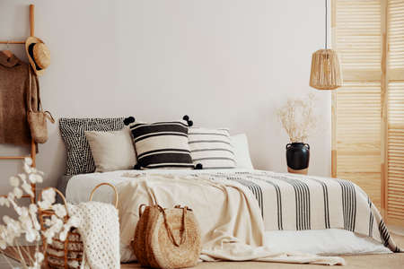 Stripped bedding on white king size bed, copy space on empty wall