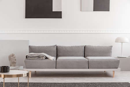 Grijze bank in wit interieur met abstracte schilderijen aan de muur