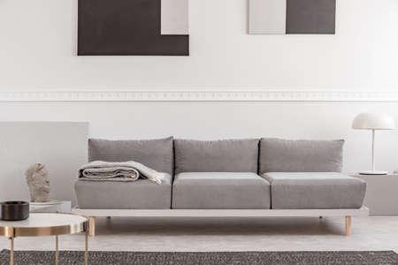 Szara sofa w białym wnętrzu z abstrakcyjnymi obrazami na ścianie
