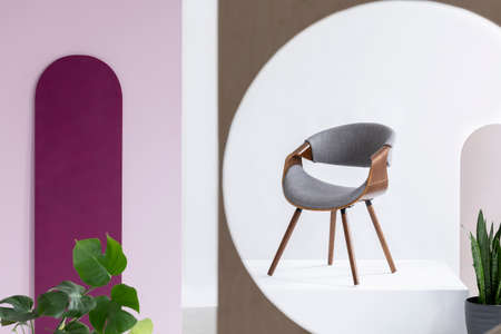 Stylish wooden grey chair in fashionable abstract interior