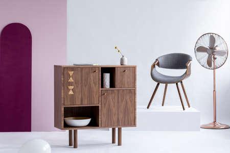 Stylish wooden commode next to grey chair on white platform in trendy interior Zdjęcie Seryjne