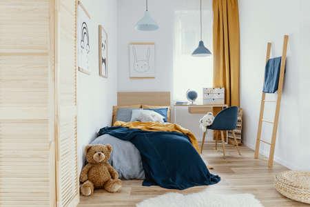 Interior de dormitorio y área de trabajo multifuncional con cama y escritorio Foto de archivo