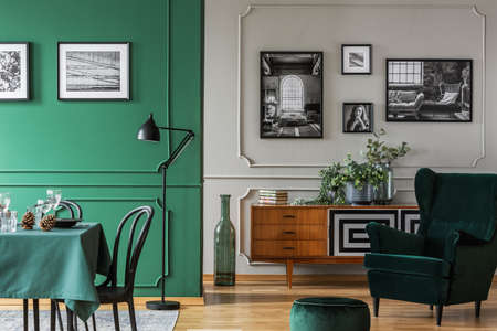 Lots of photos on the walls of a bright, open space flat interior with a living and dining area. Real photo