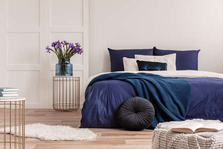 Flowers in vase on bedside table next to king size bed with navy blue bedding