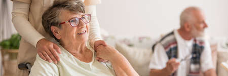 Panoramic view of elderly lady on wheelchair holding hands with supporting volunteer standing behind her Banco de Imagens