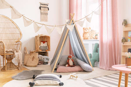Cute pink little princess playroom in scandinavian design with peacock chair, pillows, carpets, toys and tent with toys, real photo