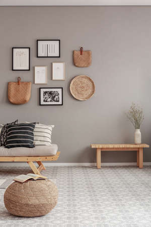 Gallery of black and white posters and wicker accessories on beige wall of Scandinavian living room
