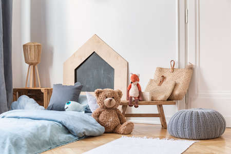 Stylish kid's bedroom in tenement house. Grey pouf on the parquet, wooden table with bags and toys, bed with blue bedding. Archivio Fotografico