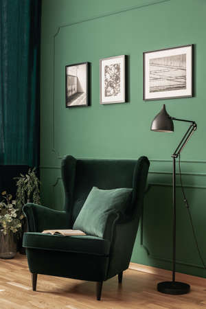 Foto reale di un elegante angolo lettura verde con lampada in metallo e poltrona in pelle scamosciata verde. Interno del soggiorno