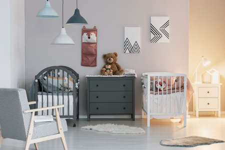 Brown teddy bear on grey wooden commode between two cribs in fashionable bedroom for twins