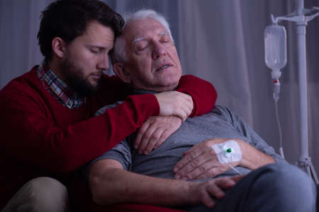 Senior sick man sleeping in his son's arms at hospital bed
