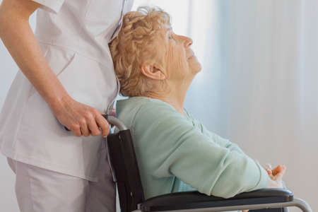 Positive senior lady on wheelchair with her helpful doctor at nursing facility