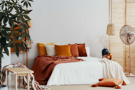 Autumn colored pillows on king size bed in chic bedroom interior Stock Photo - 126996943