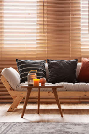 Burgundy, black and striped pillows on beige living room sofa Imagens