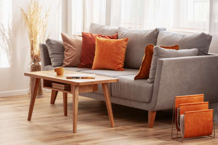 Living room with wooden coffee table and grey couch with ginger, orange and red pillows Stock Photo - 126996963
