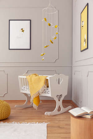 White wooden cradle with yellow cozy blanket in the middle of fashionable nursery