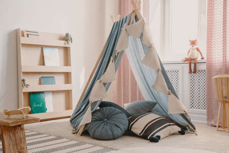 Wooden furniture and tent with pillows in natural scandinavian playroom for kids, real photo