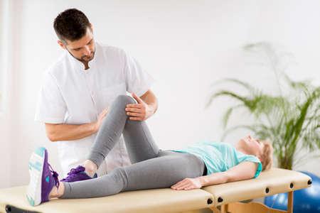 Frau mittleren Alters mit Knieverletzung, die während der Sitzung mit einem jungen, gutaussehenden Arzt auf einem Physiotherapietisch liegt