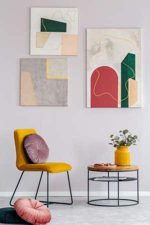 Gele stoel met rond kussen naast houten salontafel met bloemen in vaas