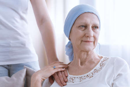 Senior woman wearing blue headscarf, suffering from lung cancer, daughter hand on her arm as a sign of support Zdjęcie Seryjne