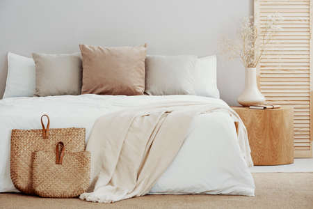 White and beige bedding on double bed in simple interior 版權商用圖片