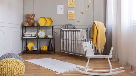 White rocking horse in elegant grey and yellow baby room with industrial shelf and wooden cradle