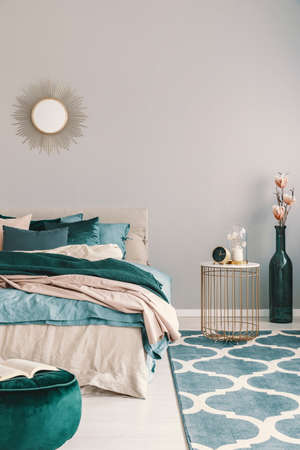 Flowers in stylish bottle like vase next to trendy nightstand with clock in beautiful bedroom interior with beige and emerald green bedding