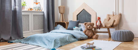 Panoramic view of kids bedroom and play room with small bed with blue bedding, teddy bear on the floor and books on the carpet