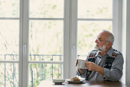 Melancholic grandfather eating breakfast at the table all alone