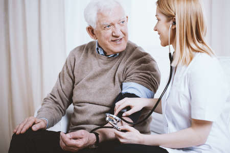Senior grey man with supporting measuring blood pressure