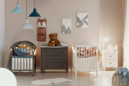Real photo of a pastel bedroom interior for siblings with wooden cribs, beige walls, and cute teddy bears on a gray chest of drawers