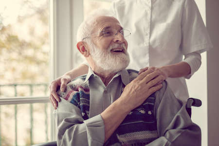 Senior man sitting on the wheelchair, laughing and holding his nurses hand