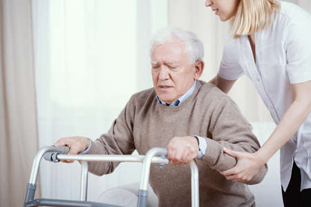 Elder grey man with walker and young nurse supporting him