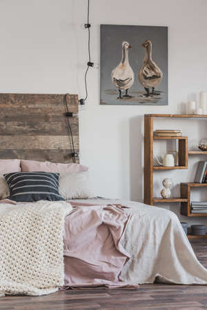 Real photo of a bright, rustic bedroom interior with pink bed, wooden furniture and painting of two ducks Foto de archivo - 127521915